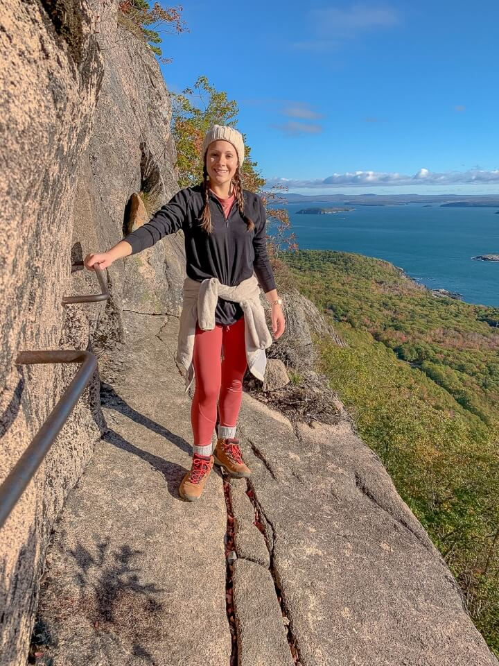 Woman standing on narrow granite rock with steep drop off to side