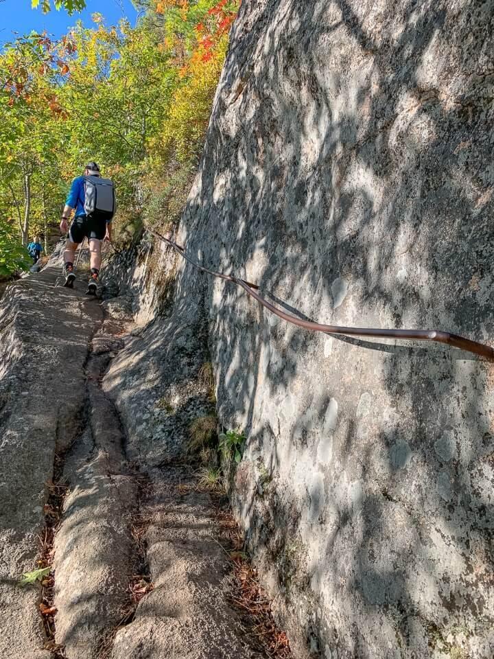 Man climbing steep rock using iron rail for assistance