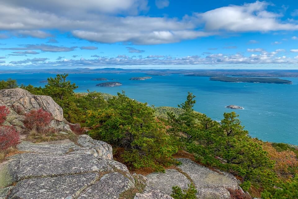 Incredibly beautiful view from the summit of Acadia National Park Precipice Trail hike rocks trees ocean and blue sky