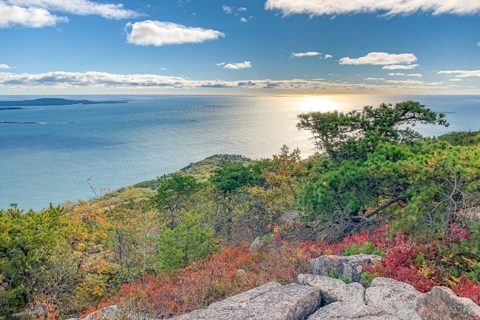 Summit view over ocean with sun reflecting at the top of precipice trail hike in acadia national park