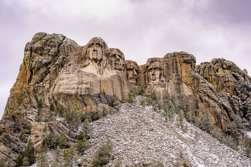 Best places to stay near mount rushmore hotels in keystone and black hills mt rushmore sculpture carved into rock with clouds full of snow