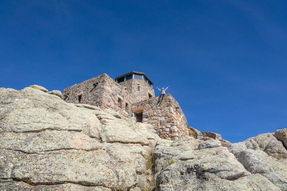 Black Elk Peak trail summit fire watchtower with woman arms stretched out blue sky