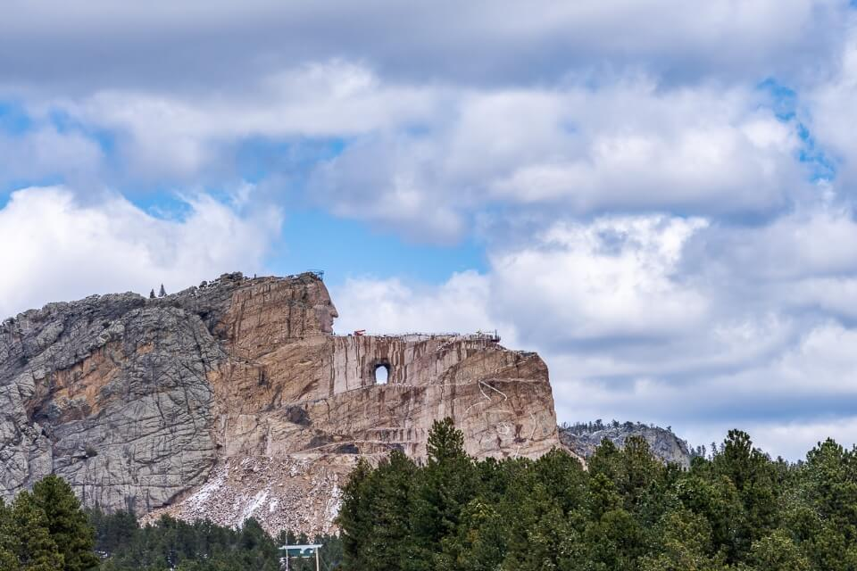 Crazy horse sculpture is a popular place to visit near mount Rushmore taken from afar with trees and puffy clouds