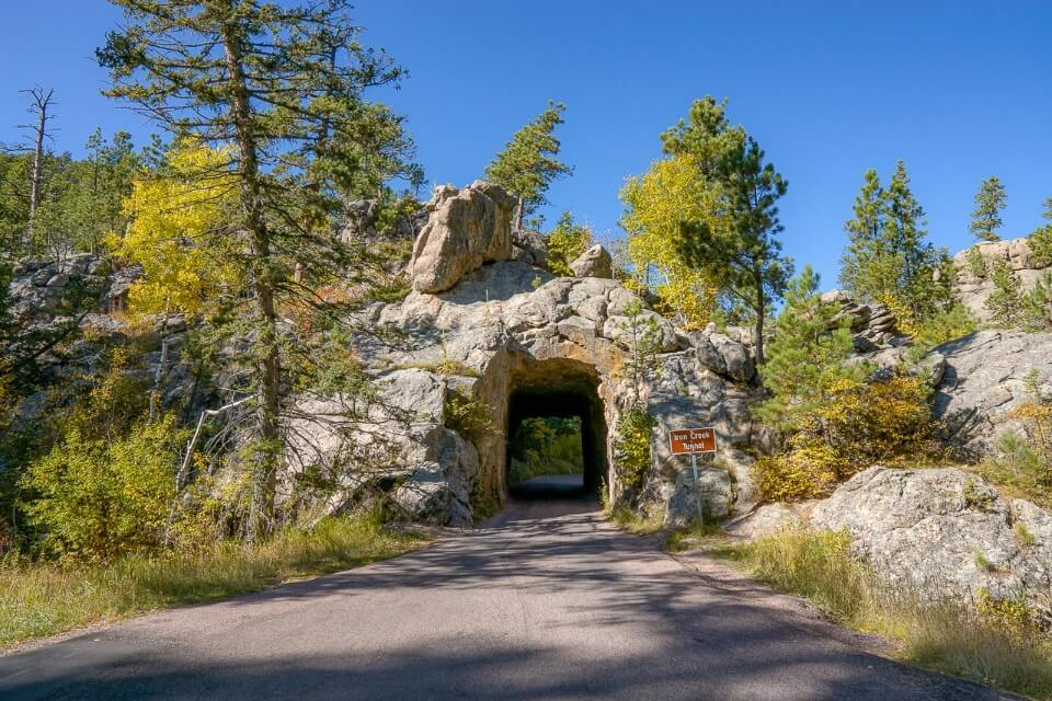 Narrow tunnel leading through granite rock on needles highway in south dakota is one of the most amazing drives near mt rushmore