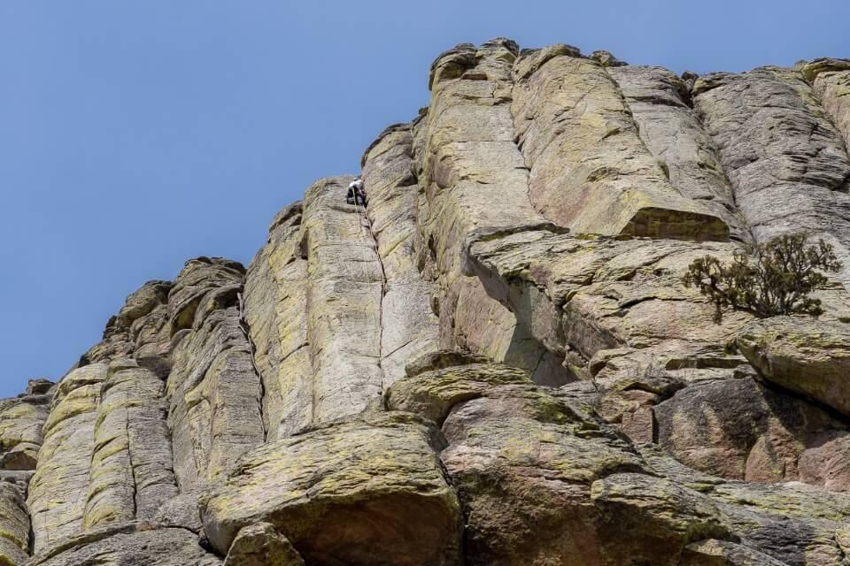 Man climbing on rock face with hexagonal shaped cracks