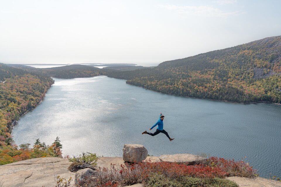 Where Are Those Morgans jumping from one rock to another at the summit of South Bubble trail one of the best hikes in acadia national park with lake background perspective photograph