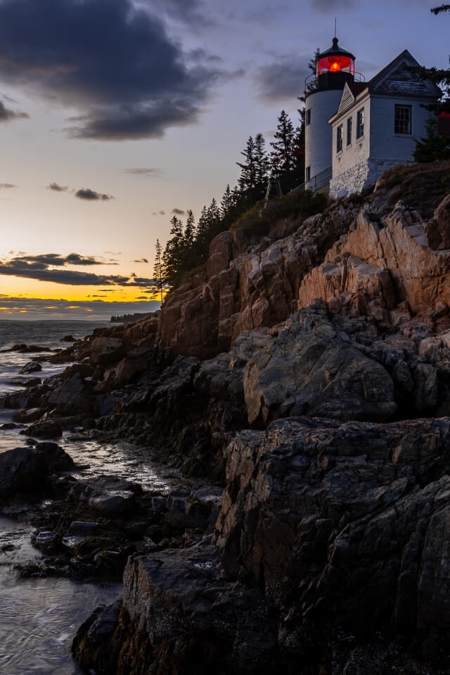 Photography at Bass Harbor Head Lighthouse is one of the most amazing things to do in acadia national park stunning white lighthouse on a cliff edge colorful sky