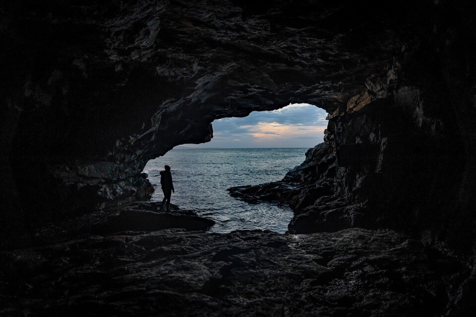 Hidden cave in Acadia National Park woman silhouetted against ocean at sunrise best things to do in acadia