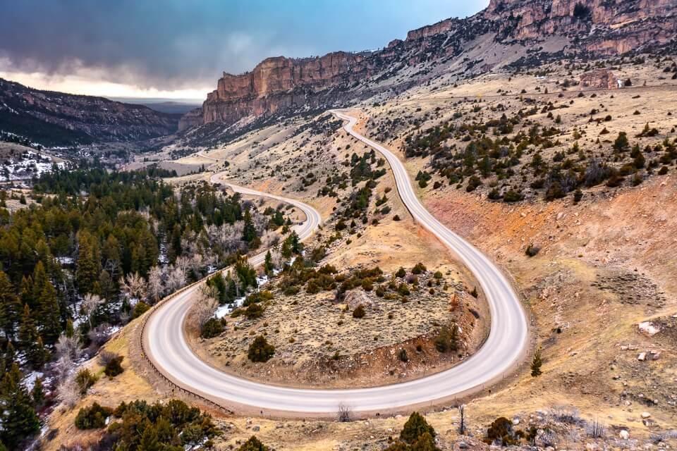 U shaped bend in Cloud Peak Skyway scenic byway in Wyoming taken by drone with clouds in sky